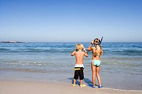 Boy 4-6 and girl 5-7 standing side by side on sandy beach at water's edge, wearing snorkels, rear view