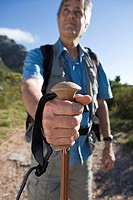 Mature man standing on mountain trail, holding hiking pole, close-up, front view