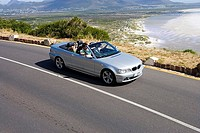 South Africa, Cape Town, family man driving silver convertible on coastal road, elevated view