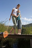 Mother and daughter 7-9 embracing on small wooden footbridge above stream, woman with fishing net, smiling, portrait