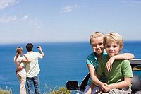 Parents photographing Atlantic Ocean from clifftop, focus on children 6-9 sitting in parked convertible, portrait