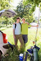 Father and teenage son 15-17 unloading car on fishing trip in rural setting, smiling, portrait