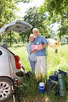 Multi-generational family unloading car on camping trip, focus on grandparents embracing beside car boot, portrait