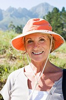 Senior woman wearing orange sun hat, standing in rural setting, smiling, close-up, front view, portrait