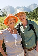 Senior couple, in sun hats, standing on hiking trail in mountains, smiling, portrait