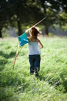 Girl 7-9 running with kite in field, rear view