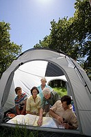 Multi-generational family sitting inside tent in woodland clearing, looking at map, smiling