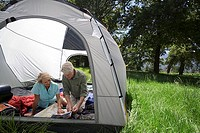 Senior couple sitting inside tent in woodland clearing, looking at map, smiling
