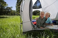 Senior couple sitting inside tent in woodland clearing, looking at map, smiling, portrait