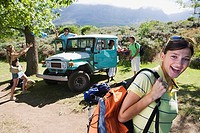 Group of young adults departing on hiking trip, man unloading jeep, focus on woman in foreground, smiling