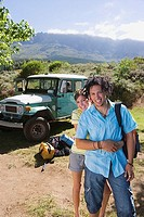 Young couple standing near parked jeep at start of camping holiday, woman embracing man, smiling, portrait
