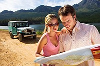 Young couple standing near parked jeep on dirt track beside lake, consulting map
