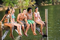 Five young adults, in swimwear, sitting side by side on lake jetty, smiling, portrait
