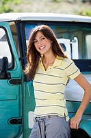 Young woman leaning against parked jeep, smiling, portrait
