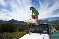 Young couple sitting on roof of parked jeep in mountain valley, consulting road map