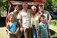 Multi-generational family standing beside parked SUV, smiling, portrait