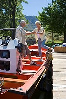 Senior woman boarding motorboat moored at lake jetty, husband offering helping hand, smiling, side view