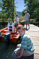 Boy 8-10 sitting on lake jetty, smiling, side view, portrait, father and grandfather loading fishing rods into motorboat