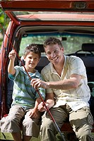 Father and son 8-10 sitting in boot of parked SUV, holding fishing rods, smiling, portrait