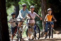 Family, in cycling helmets, mountain biking on woodland trail, smiling, portrait