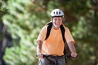 Senior man, in orange t-shirt and cycling helmet, mountain biking on woodland trail, smiling, front view, portrait