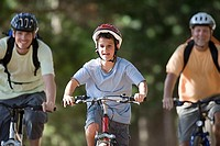 Boy 8-10, in cycling helmet, mountain biking on woodland trail with father and grandfather, front view