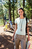 Family hiking on woodland trail, focus on woman in foreground, smiling, portrait