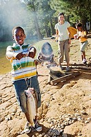 Family cooking food on camping trip beside lake, boy 8-10 holding aloft fish in foreground, smiling, portrait