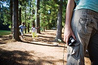Family hiking on woodland trail, focus on woman holding binoculars in foreground, mid-section