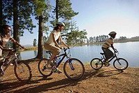 Family mountain biking along lakeside woodland trail, side view