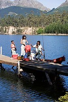 Family loading life jackets and provisions on moored motorboat beside lake jetty