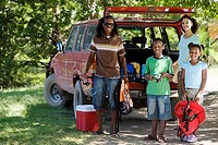 Family unloading parked SUV on camping trip, girl 7-9 holding life jacket, smiling, portrait