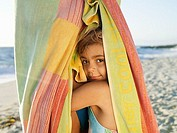 Girl 5-7 snuggling up to mother wrapped in large towel on sandy beach, smiling, close-up, side view, portrait