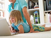 Senior woman and granddaughter 6-8 using laptop on living room floor, smiling, side view surface level
