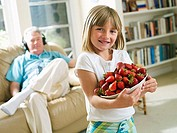 Senior man relaxing on sofa at home, focus on granddaughter 6-8 holding bowl of strawberries, smiling, portrait