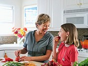 Senior woman preparing food on kitchen worktop, granddaughter 8-10 tasting fresh strawberry, smiling