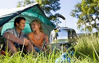 Young couple sitting inside dome tent in woodland clearing, focus on kettle boiling on camping stove surface level