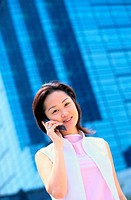 Woman Talking on a Cellular Phone by a Skyscraper