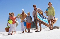 Three generation family walking on beach, carrying deckchair, bags, towels and balls, smiling