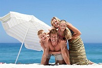 Two generation family posing on sandy beach beside sunshade, smiling, portrait