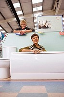 Couple shopping in home furnishings store, woman sitting in bathtub, smiling, portrait (thumbnail)