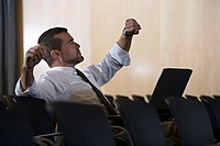 Businessman checking time on watch in empty conference room, stretching, laptop in lap, side view