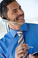 Businessman wearing telephone headset, using personal electronic organiser, smiling, close-up tilt