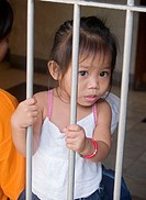 curious little girl behind a gate, Sinulog Festival, Cebu, Philippines