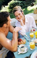 Young couple enjoying breakfast in outdoor setting