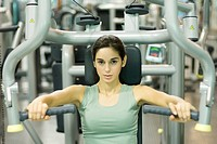 Young woman working out with weight machine