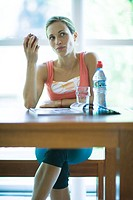 Young woman in exercise clothing having snack in health club cafeteria