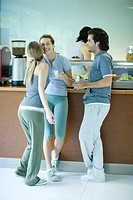 Young adults in exercise clothing, taking break in health club cafeteria