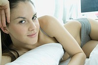 Young woman lounging on bed in underwear