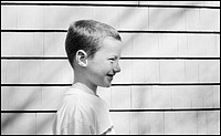 Profile of young boy outdoors, smiling'